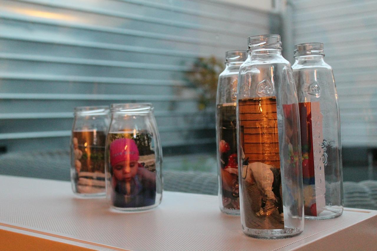Szklane butelki oraz słoiki ze zdjęciami.